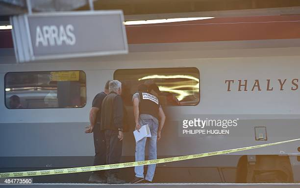 Crime investigators look into the window of a Thalys train of French national railway operator SNCF at the main train station in Arras northern...