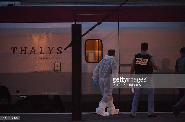 Crime investigators walk on a platform next to a Thalys train of French national railway operator SNCF at the main train station in Arras northern...
