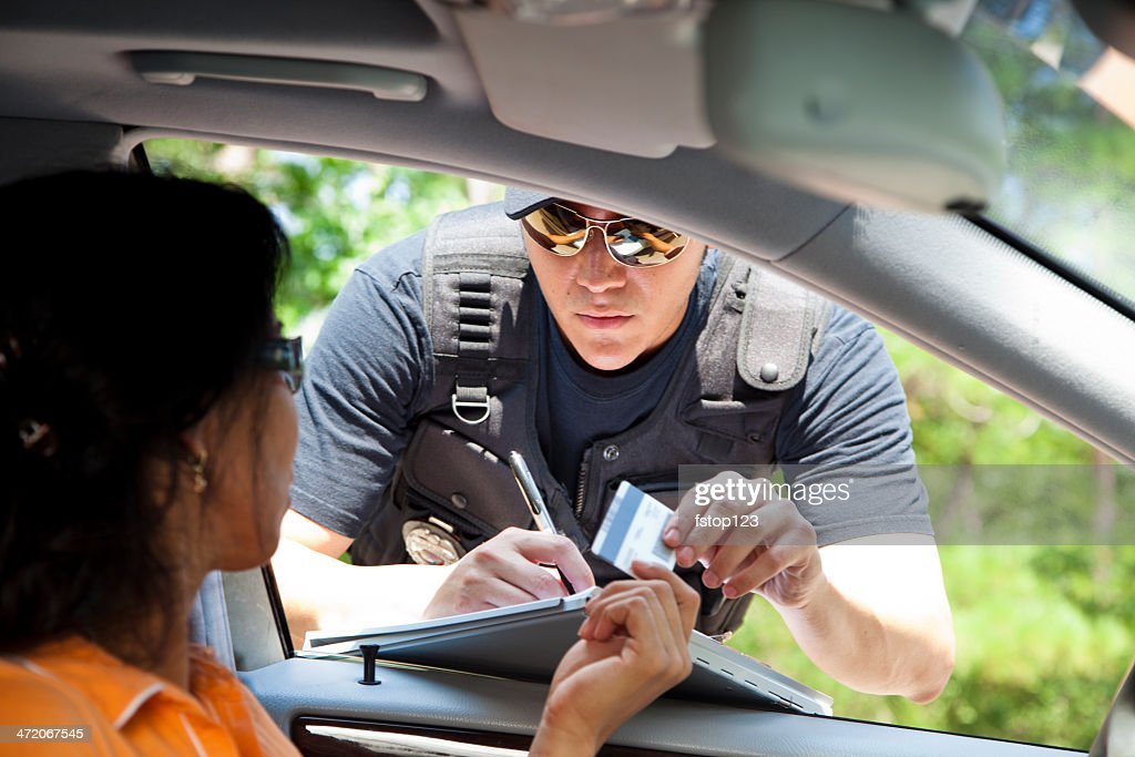 Crime: Policeman gives driver a traffic ticket. : Stock Photo