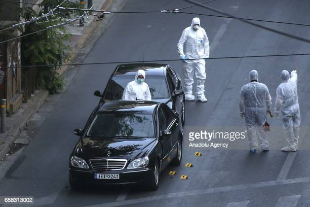 Crime scene investigators inspect a Mercedes SClass vehicle of former Greek Prime Minister Lucas Papademos after an explosion of a bombing attack in...