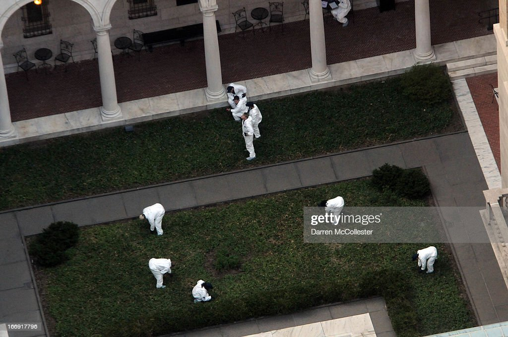 Crime scene investigators inspect the courtyard of the Boston Public Library near the site of the Boston Marathon finish line bombing April 18, 2013 in Boston, Massachusetts. Officials today released the images of two suspects in the Boston Marathon bombing that killed three people and wounded hundreds more.