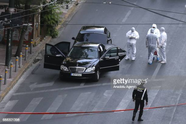 Crime scene investigators inspects a Mercedes Sseries of former Greek Prime Minister Lucas Papademos after an explosion caused by a bombing attack in...