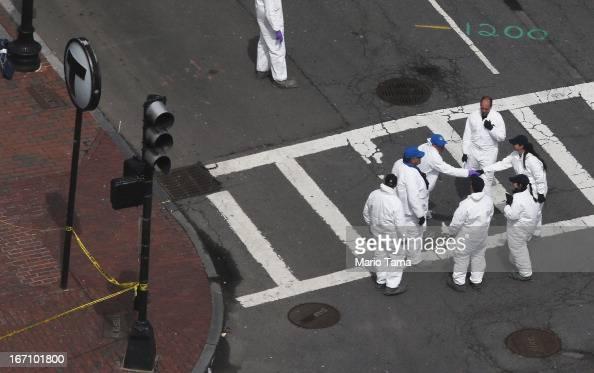 Crime scene investigators shake hands on Dartmouth Street at the corner Boylston Street near the scene of the Boston Marathon bombings on the day...