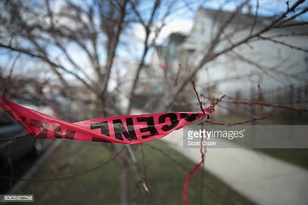 Crime scene tape clings to a tree where a Christmas day shooting left Fabiian Ortega dead on December 27 2016 in Chicago Illinois At least 11 people...