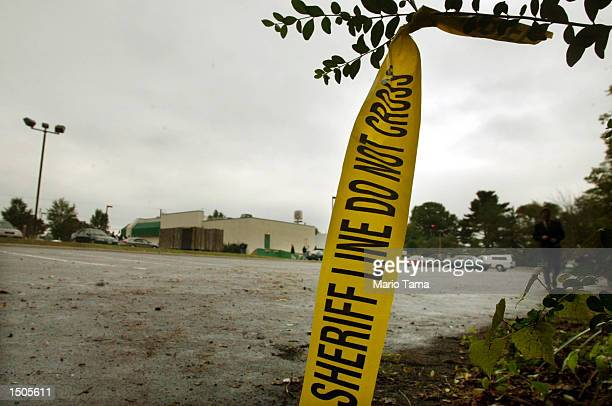 Crime scene tape is seen at the edge of a wooded area behind the parking lot of a Ponderosa restaurant where a suspected sniper shooting occurred...