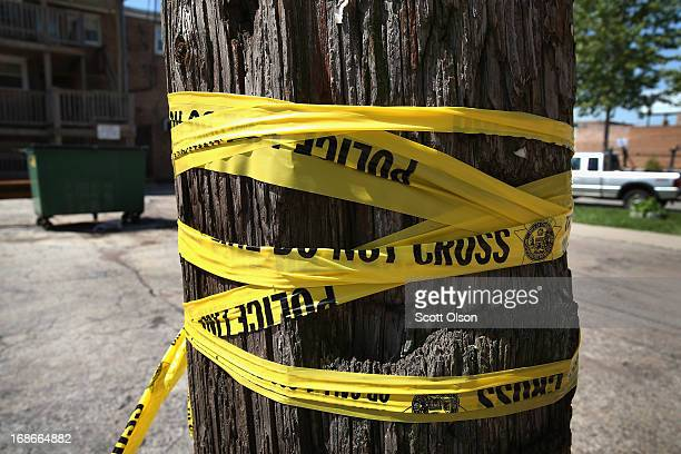 Crime scene tape is wrapped around a power pole near the location where a 20yearold man died from a gunshot wound to the head and a 15yearold boy was...