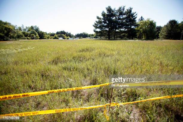Crime scene tape marks the area beyond which news media may not go where FBI agents search a field outside Detroit for the alleged remains of former...