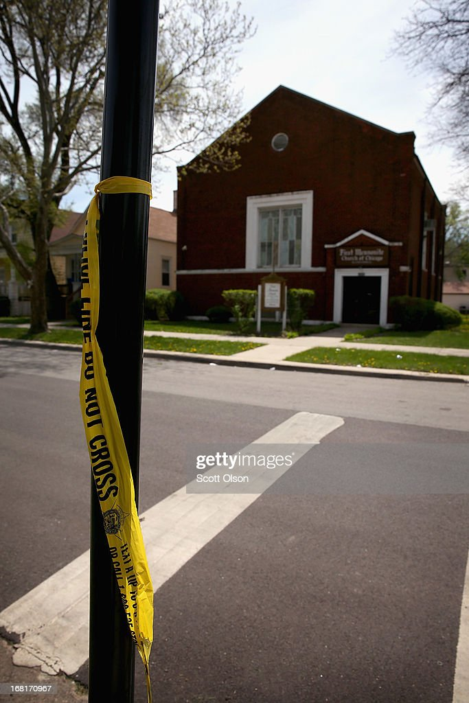 Crime scene tape remains tied to a sign post in front of the First Mennonite Church of Chicago following the shooting of three men shortly after midnight in the Englewood neighborhood on May 6, 2013 in Chicago, Illinois. Less than two blocks away on Saturday, a 47-year-old woman, Denise Warfield, was found stabbed to death in an abandoned church building.