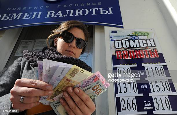 A Crimean resident holds Ukrainian Hryvnia money next to a money exchange office as she prepares to buy western currency and Russian roubles in...