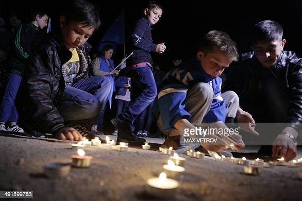 Crimean Tatar boys light candles during a memorial ceremony marking the 70th anniversary of the deportation of Tatars from Crimea near a Mosque in...