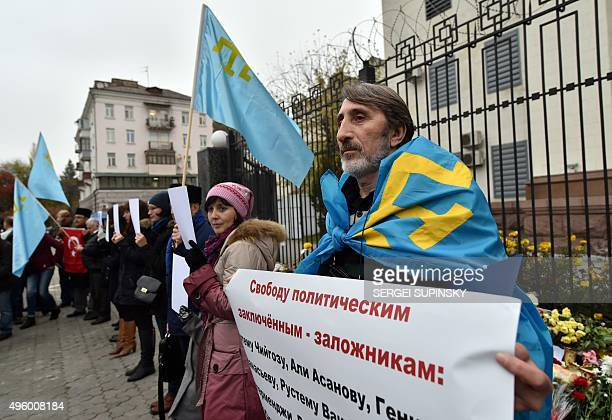A Crimean Tatar covered with the flag of the Crimean Tatars holds a placard reading 'Free political prisonershostages' during a demonstration of...