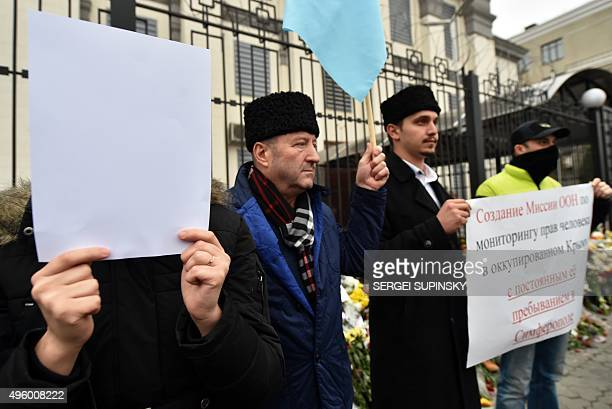 A Crimean Tatar covers her face with a blank sheet during a demonstration of Crimean Tatars in front of the Russian embassy in Kiev on November 6 to...