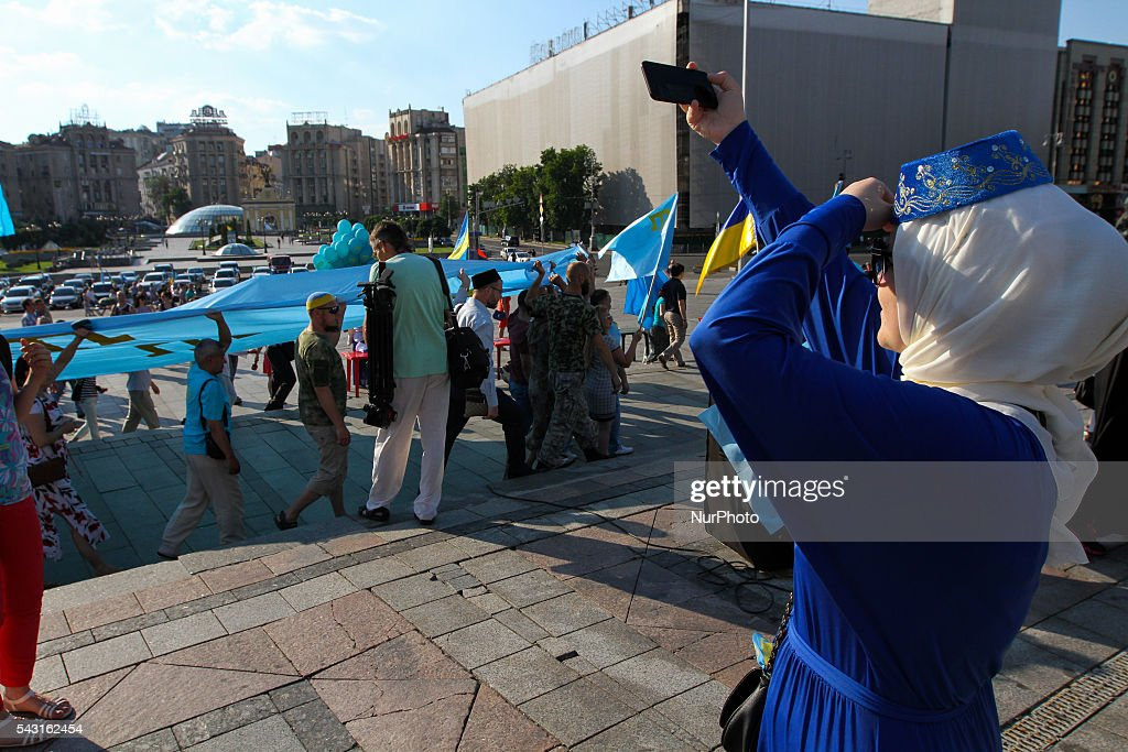 Crimean Tatars community members and supporters carry a huge Crimean Tatars Flag as they march downtown Kyiv. Crimean Tatars community in Ukraine celebrate the Crimean Tatars Flag Day on June 26, 2016.