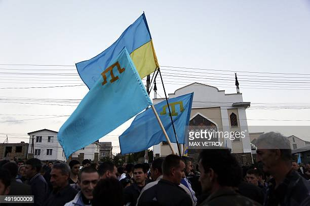 Crimean Tatars hold a Ukrainian and Tatar flags as they attend a memorial ceremony marking the 70th anniversary of the deportation of Tatars from...