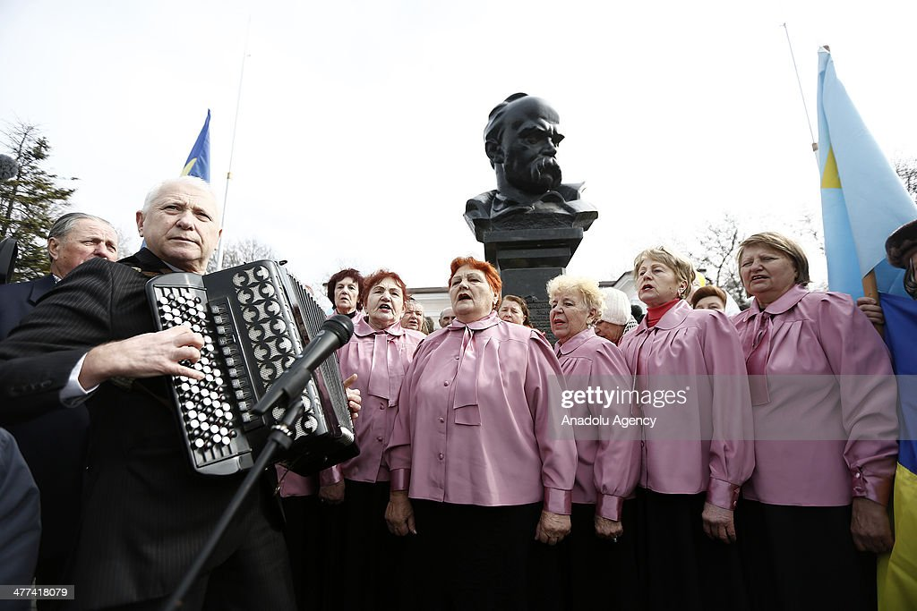Crimean who supports Ukraine sing an anthem near the Taras Sevcenko's bust in Crimea, Ukraine, on March 9, 2014. Protestors hold a public demonstration due to support Russia and Ukraine during the preparation of referendum in Crimea, Ukraine, on March 9, 2014. Crimeans who support Russia shout slogans in Lenin Square.