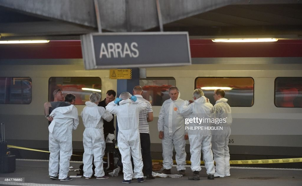 Criminal and forensic investigators dressed in protective suits stand on a platform next to a Thalys train of French national railway operator SNCF...