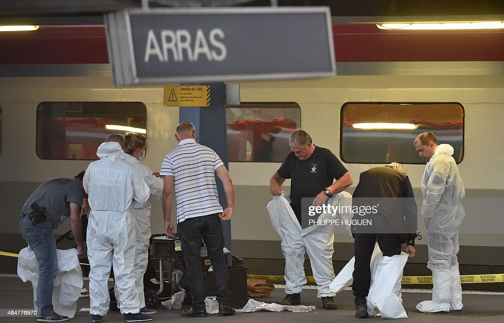 Criminal and forensic investigators put on protective suits on a platform next to a Thalys train of French national railway operator SNCF at the main...