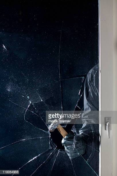 A criminal breaking into a window, focus on hand