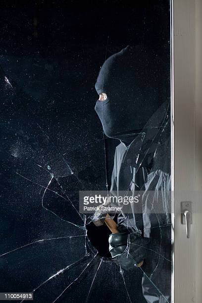 A criminal breaking into a window with a hammer