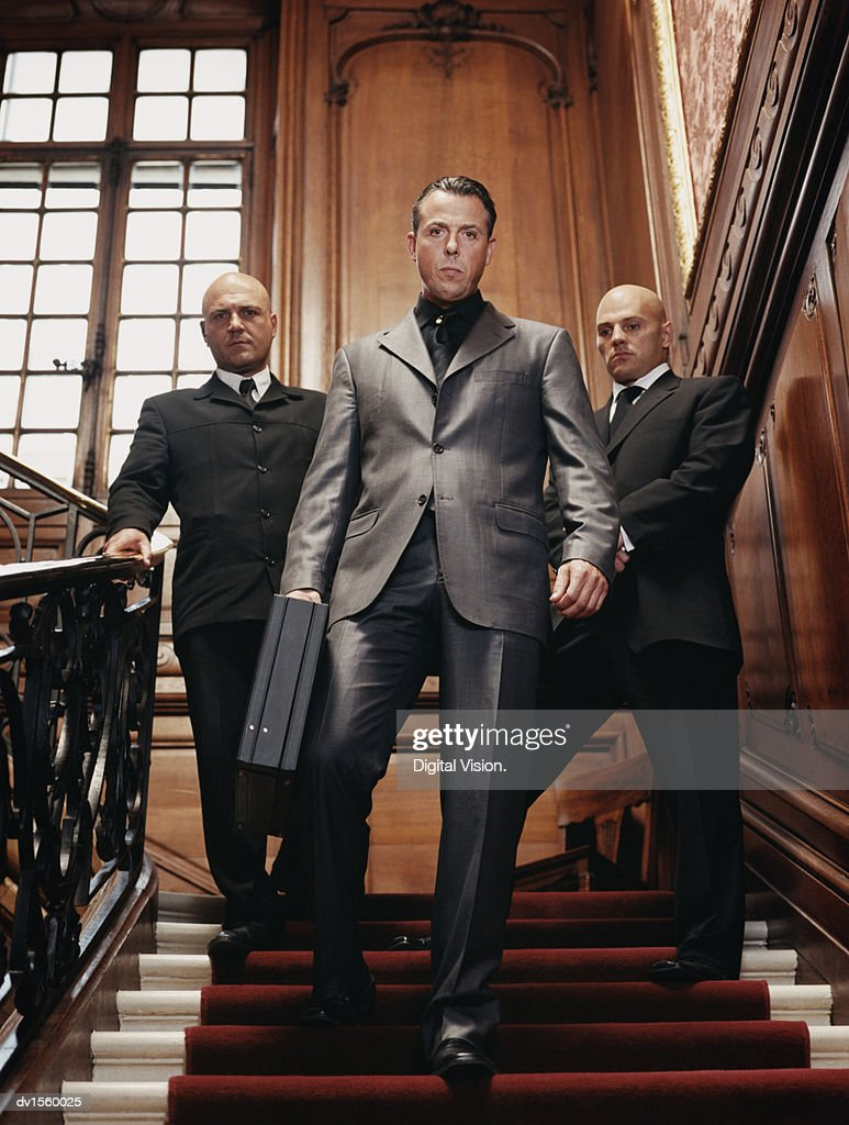 Criminal Businessman Descending Stairs Holding a Briefcase and Bodyguards Behind Him