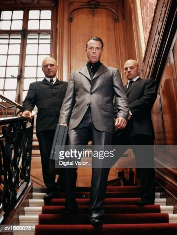 Criminal Businessman Descending Stairs Holding a Briefcase and Bodyguards Behind Him : Stock Photo