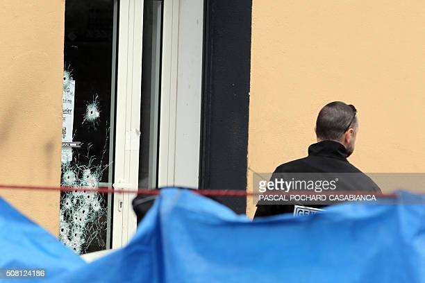 A Criminal Identification policeman looks for evidence at a Muslim butcher's shop that was sprayed with bullets overnight on February 3 2016 in...