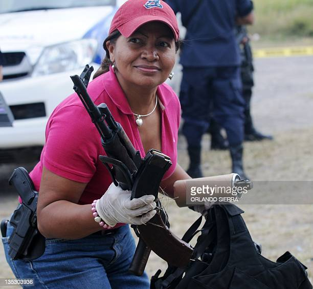 A criminal investigation agent holds the AK47 and a tear gas bomb belonging to the seven captured man with an AK47 9mm guns tear gas bombs gas masks...