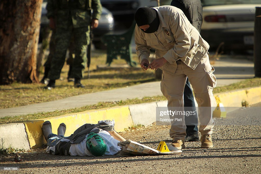 A criminal investigator takes a picture of a body with a mask in the street, one of numerous murders over a 24 hour period, on March 26, 2010 in Juarez, Mexico. Secretary of State Hillary Rodham Clinton, Defense Secretary Robert Gates, and Homeland Security Secretary Janet Napolitano all visited Mexico on March 23 for discussions centered on Mexico's endemic drug-related violence. The border city of Juarez, Mexico has been racked by violent drug related crime recently and has quickly become one of the most dangerous cities in the world to live. As drug cartels have been fighting over ever lucrative drug corridors along the United States border, the murder rate in Juarez has risen to 173 slayings for every 100,000 residents. President Felipe Calderon's strategy of sending 7000 troops to Juarez has not mitigated the situation. With a population of 1.3 million, 2,600 people died in drug-related violence last year and 500 so far this year, including two Americans recently who worked for the U.S. Consulate and were killed as they returned from a children's party.