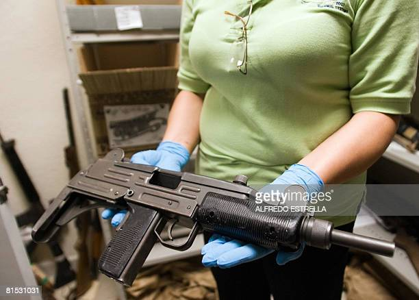 A criminologist shows a 'Uzi' submachine gun used by local drug traffickers at the Criminology Laboratory on May 28 2008 in Ciudad Juarez state of...