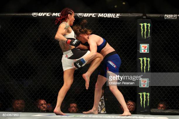 Cris Cyborg of Brazil knees Tonya Evinger in their UFC women's featherweight championship bout during the UFC 214 event at Honda Center on July 29...