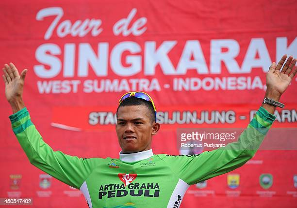 Cris Joven of Team 7 Eleven Roadbike Phillipine celebrates on the podium as he wins the Green Jersey at stage 7 of the 2014 Tour de Singkarak from...