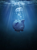 Piggy bank drowning in the ocean with copy space