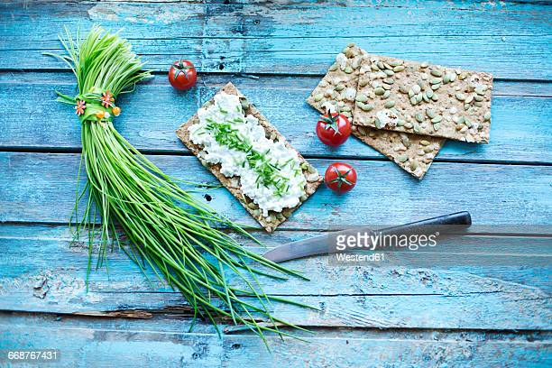 Crispbread, cream cheese, bunch of chive, cocktail tomatos and knife on turquoise wood