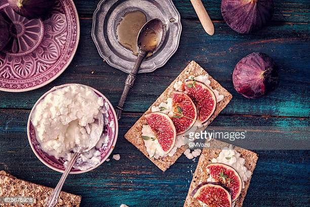 Crispbread with Cottage Cheese, Figs and Sweet Honey Served on a Table