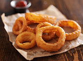 crispy onion rings with ketchup on parchment paper close up and in horizontal composition