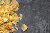 crispy potato chips on a grey cement background, top view with copy space