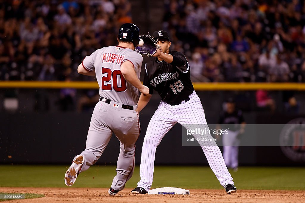 Cristhian Adames of the Colorado Rockies snags a ball over the shoulder of Daniel Murphy of the Washington Nationals but misses the bag at second...