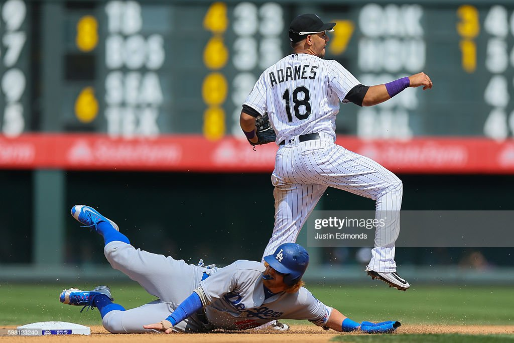 Cristhian Adames #18 of the Colorado Rockies throws to first base to complete the double play as Justin Turner #10 of the Los Angeles Dodgers slides in during the fourth inning at Coors Field on August 31, 2016 in Denver, Colorado.