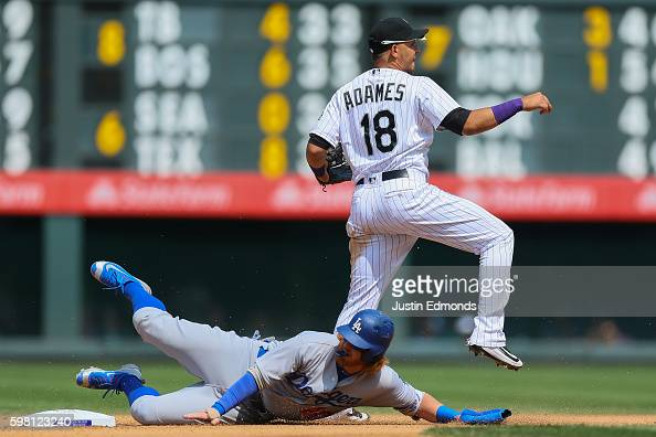 Cristhian Adames of the Colorado Rockies throws to first base to complete the double play as Justin Turner of the Los Angeles Dodgers slides in...