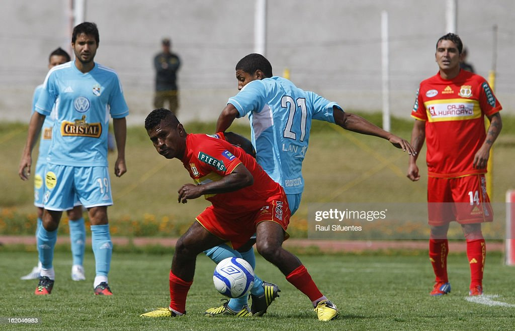 Cristian Adrianzen of Sporting Cristal fights for the ball with Jose Mendoza of Sport Huancayo during a match between Sport Huancayo and Sporting Cristal as part of The Torneo Descentralizado 2013 at the Huancayo Stadium on February 18, 2013 in Huancayo, Peru