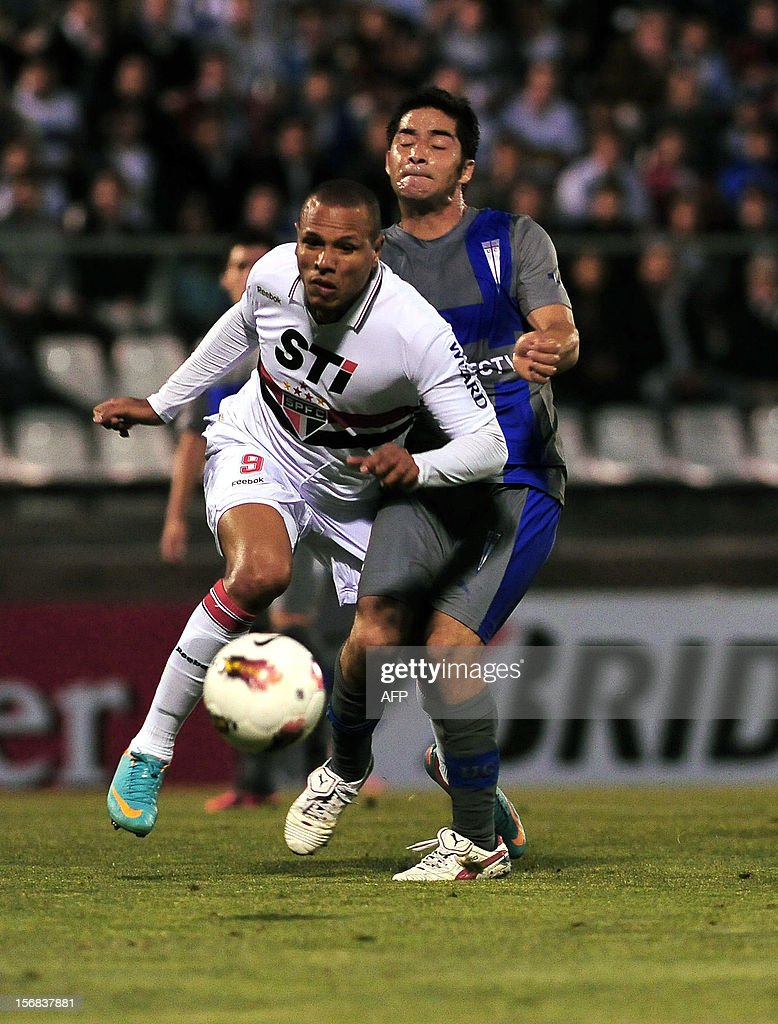 Cristian Alvarez (R) of Universidad Catolica vies for the ball with Luis Fabiano of Brazilian Sao Paulo during their Copa Sudamericana semifinal football match at the San Carlos de Apoquindo stadium in Santiago, Chile, on November 22, 2012. AFP PHOTO /Claudio SANTANA