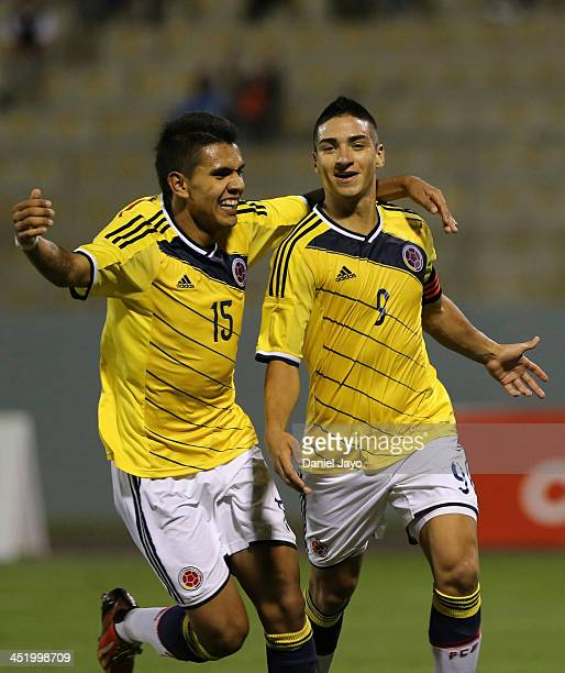Cristian Arango of Colombia celebrates with teammate Sergio Villarreal after scoring his third goal during the football final match between Colombia...