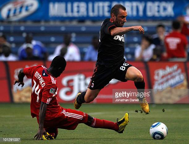 Cristian Brocci of AC Milan jumps in the air to move the ball past Patrick Nyarko of the Chicago Fire in the first half during an international...