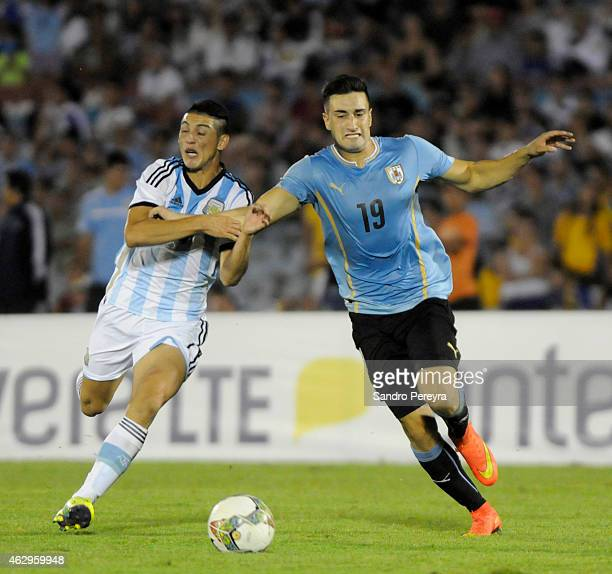 Cristian Espinoza of Argentina and Erick Cavaco of Uruguay fight for the ball during a match between Argentina and Uruguay as part of South American...
