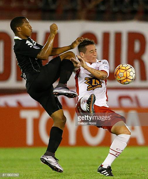Cristian Espinoza of Huracan fights for the ball with Andres Felipe Ibarguen of Atletico Nacional during a group stage match between Huracan and...