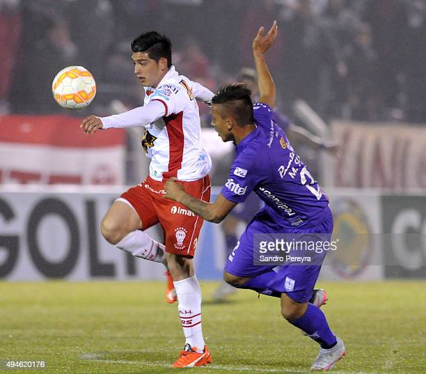 Cristian Espinoza of Huracan fights for the ball with Mathias Suarez of Defensor Sporting during a second leg match between Defensor Sporting and...