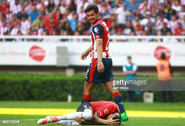 Cristian Gonzalez of Atlas lies on the grass while observed by Oswaldo Alanis of Chivas during the quarter finals second leg match between Chivas and...