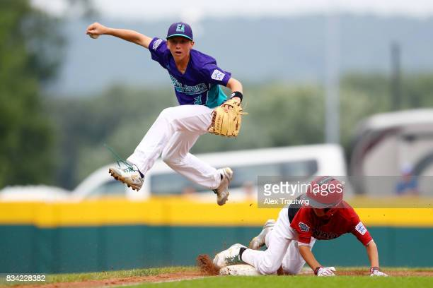 Cristian Laghi of the Europe Africa team from Italy jumps as Nathaniel Factor of the Canada team from British Columbia slides into third base during...