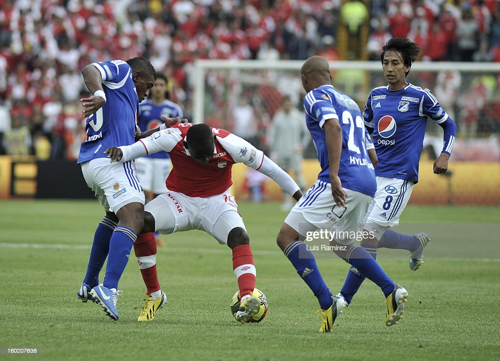 "Cristian Martinez (C) of Independiente Santa Fe fights for the ball with Elkin Blanco (R), Lewis Ochoa and Rafale Robayo (R) of Millonarios during the match between Independiente Santa Fe and Millonarios as part of the the Champions Super League at Nemesio Camacho ""El Campin"" stadium on January 27, 2013 in Bogota, Colombia."