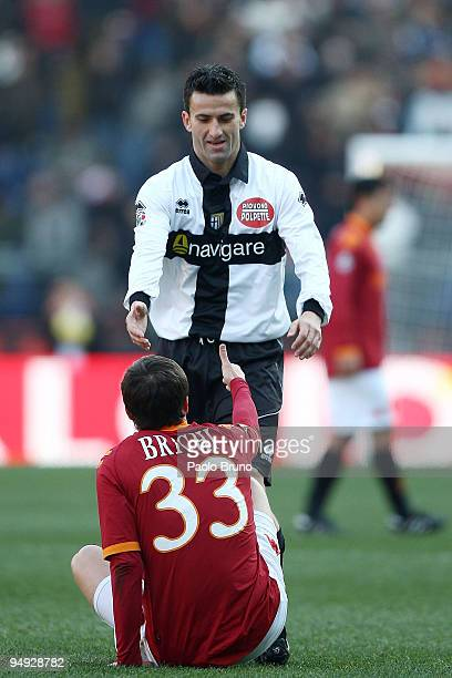 Cristian Panucci of Parma FC helps Matteo Brighi of AS Roma on the ground during the Serie A match between Roma and Parma at Stadio Olimpico on...